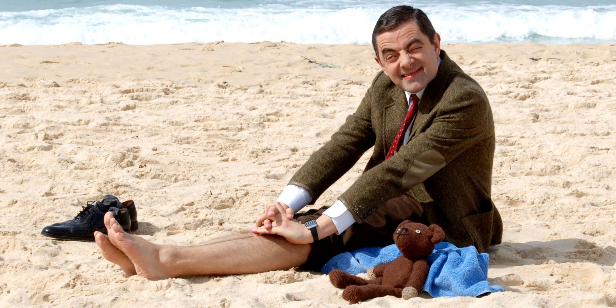 "British comedian Rowan Atkinson as his alter ego Mr. Bean poses for photographs as he sits on the sand at Bondi Beach in Sydney, Wednesday, March 7, 2007. Atkinson is in Australia to promote the opening of his new film ""Mr. Bean's Holiday."" (AP Photo)"